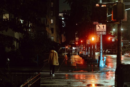 Back view of unrecognizable female walking on wet crosswalk near buildings and road signs in twilight