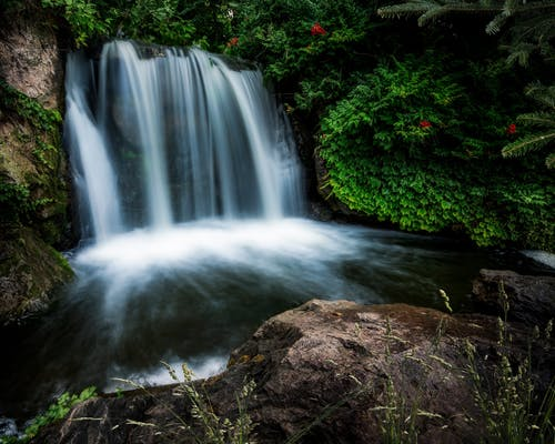 Long exposure fantastic scenery of rapid cascade flowing from rough cliff into small lake in abundant forest