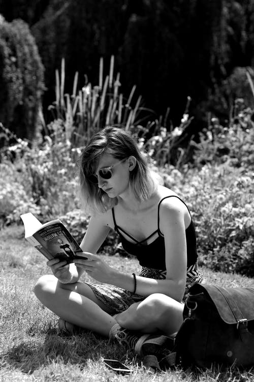 Woman in Black Tank Top Reading Book