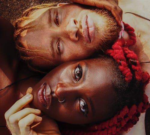 From above face of young black female with red dreadlocks and pierced nose lying close to beloved bearded man looking at camera