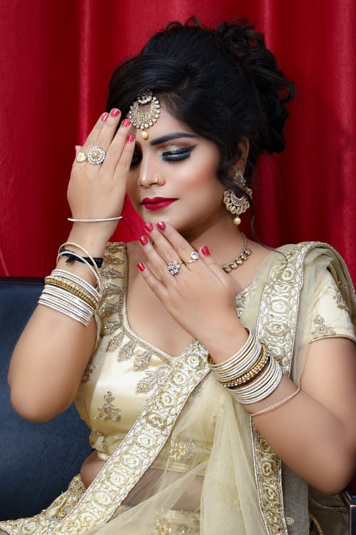 Indian female in traditional clothes covered in makeup with jewelries
