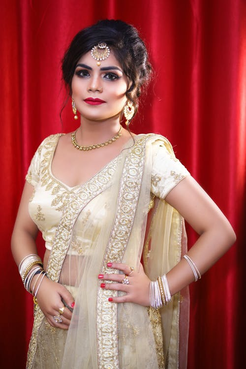 Young Indian female in traditional golden bridal clothes and sari with makeup and rings wearing necklace and bracelets with big earrings and hairdo near red curtain and looking at camera