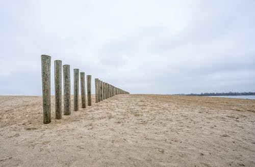 Gray Concrete Blocks on Brown Sand Under White Cloudy Sky