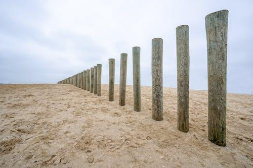 Brown Wooden Posts on Brown Sand Under White Sky