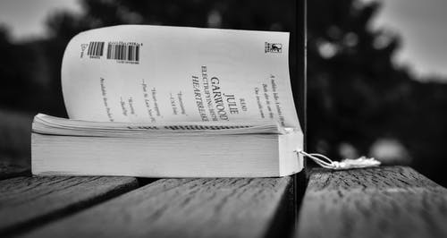 Opened book placed on wooden table in park