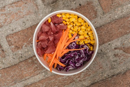 Top view of bowl with carrot meat and fresh corn placed on rough brick surface