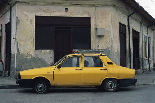 Yellow Car Parked Beside Brown Brick Building