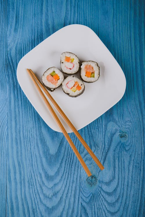 Sushi on white plate with chopsticks