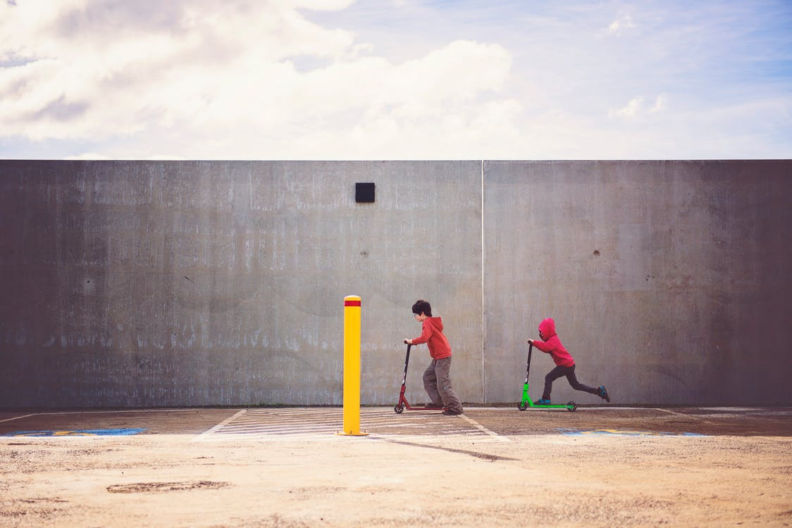 Two Boys Playing Kick Scooter