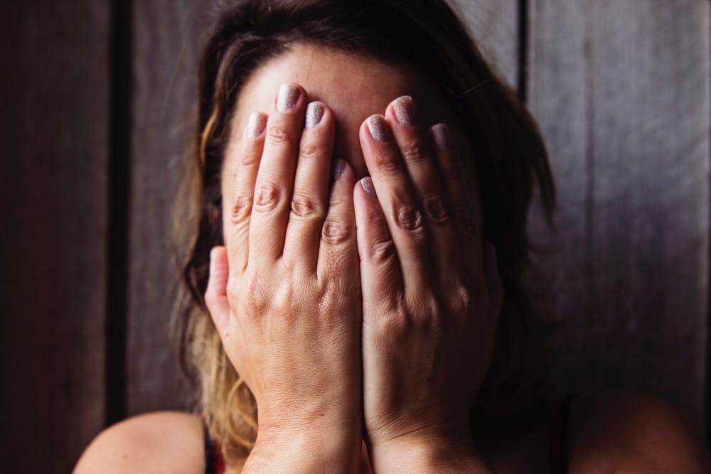Woman covering her face with hands. | Photo: Pexels
