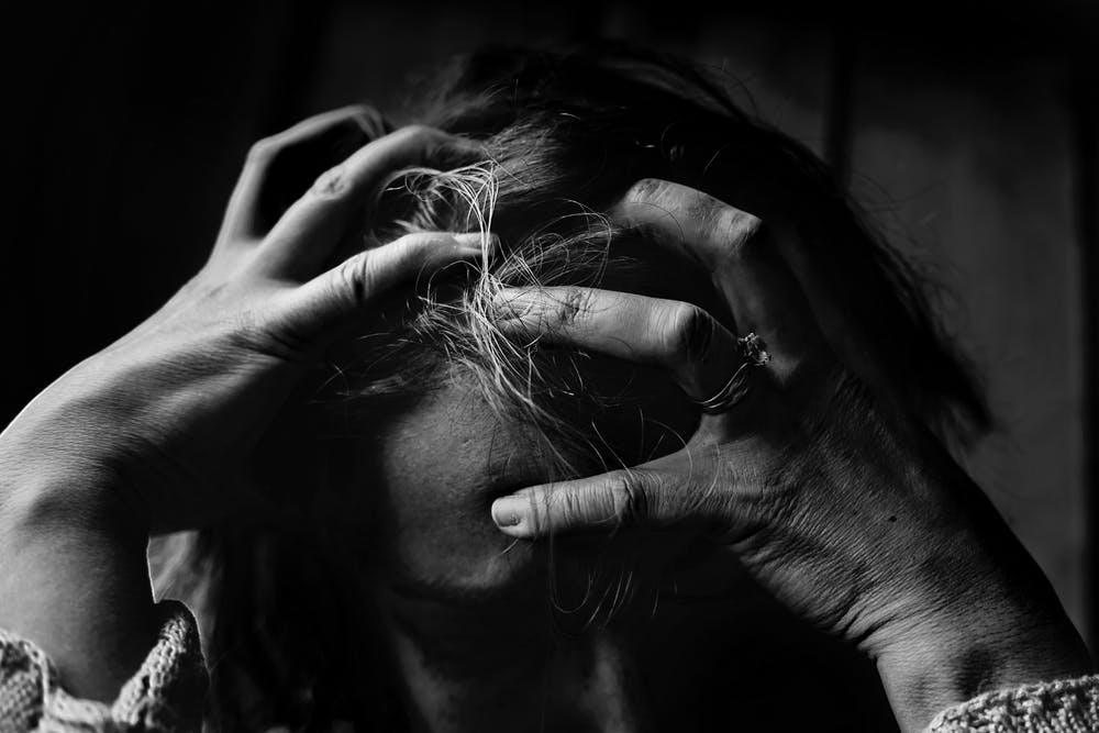 Verzweifelte Frau hält den Kopf | Quelle: Pexels