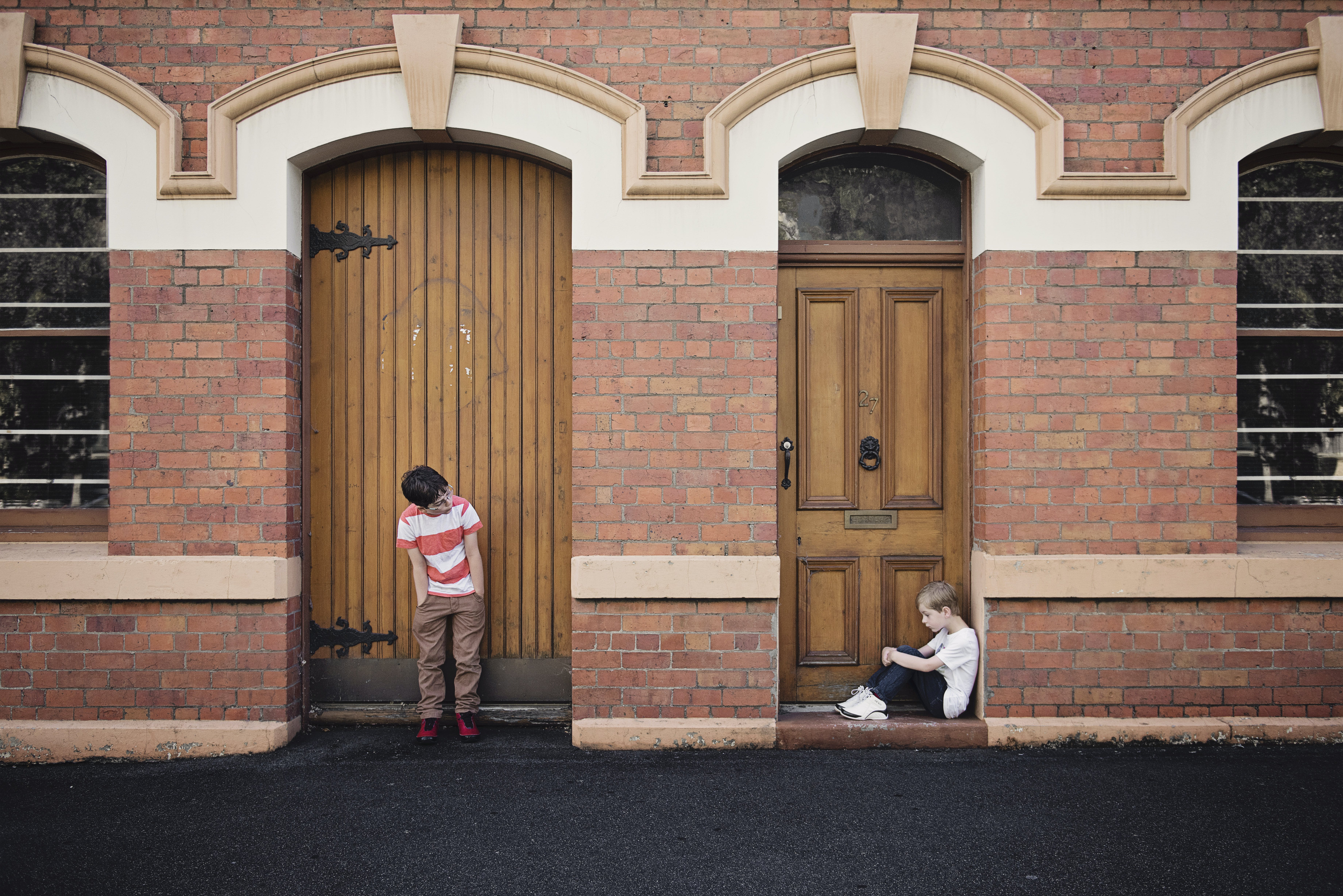 Two Children Standing and Sitting Beside Doors