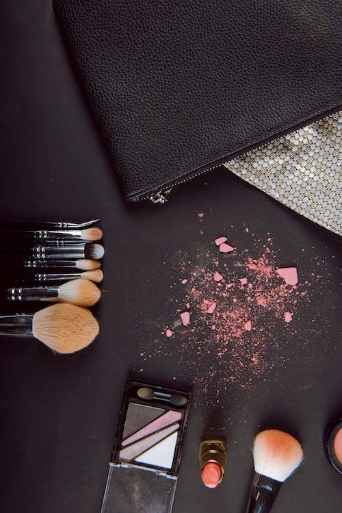 Makeup brushes near cracked eyeshadows on table