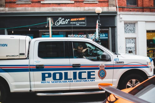 Policeman sitting in police car driving on street