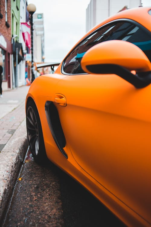 Fragment of expensive contemporary sports car parked on asphalt road in city in cloudy day