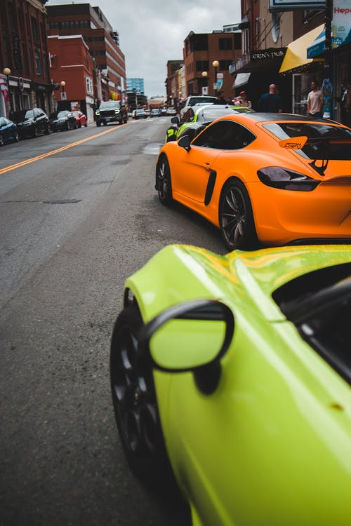 Bright modern sports car parked on asphalt road along street in cloudy day