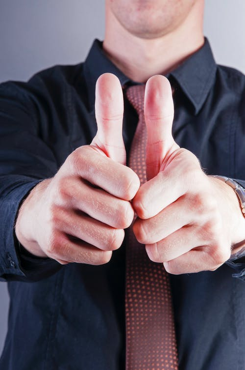 Crop stylish businessman showing thumbs up on gray background