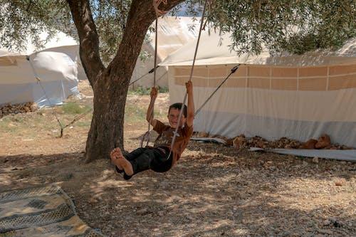 Cheerful ethnic boy swinging on swing