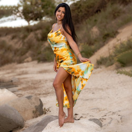 Full body of positive ethnic female wearing yellow dress looking at camera while standing on stone against blurred background on seashore