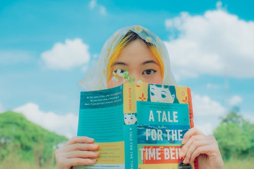 Anonymous ethnic female teenager reading book during picnic in nature