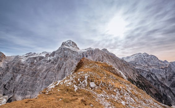 Person Standing On Top Of The Mountain Free Stock Photo
