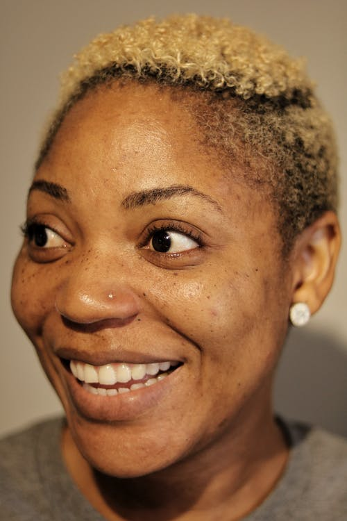 Cheerful black woman with blond hair and earrings