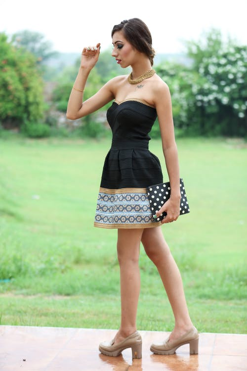 Side view full length of serious young slim female in mini dress standing on veranda with purse near green grassy meadow and bushes with plants in summer day