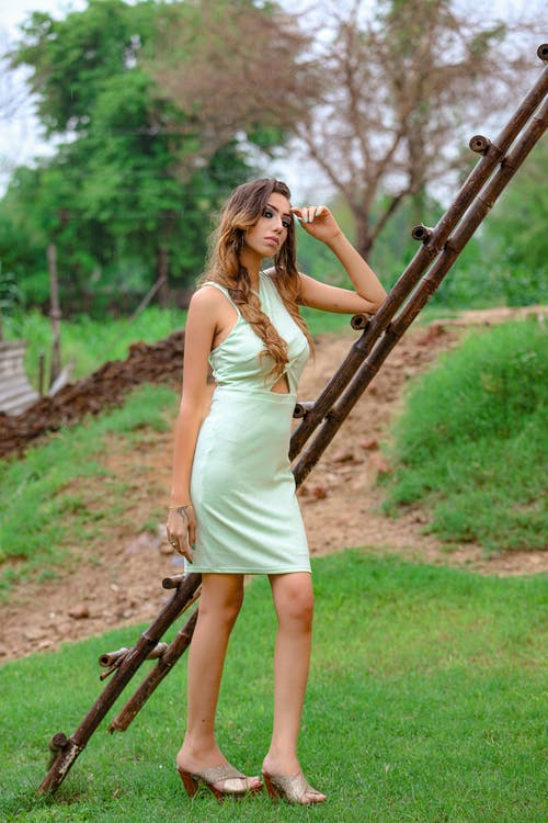 Full length of serious young female in dress standing on grassy lawn near wooden ladder with bushes and trees in summer day while looking at camera