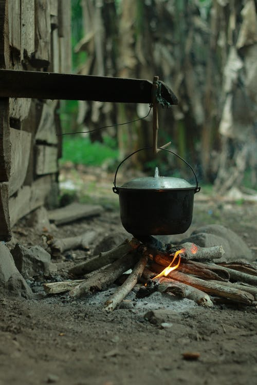 Cast iron pot with lid hanging above burning bonfire in peaceful countryside in daylight