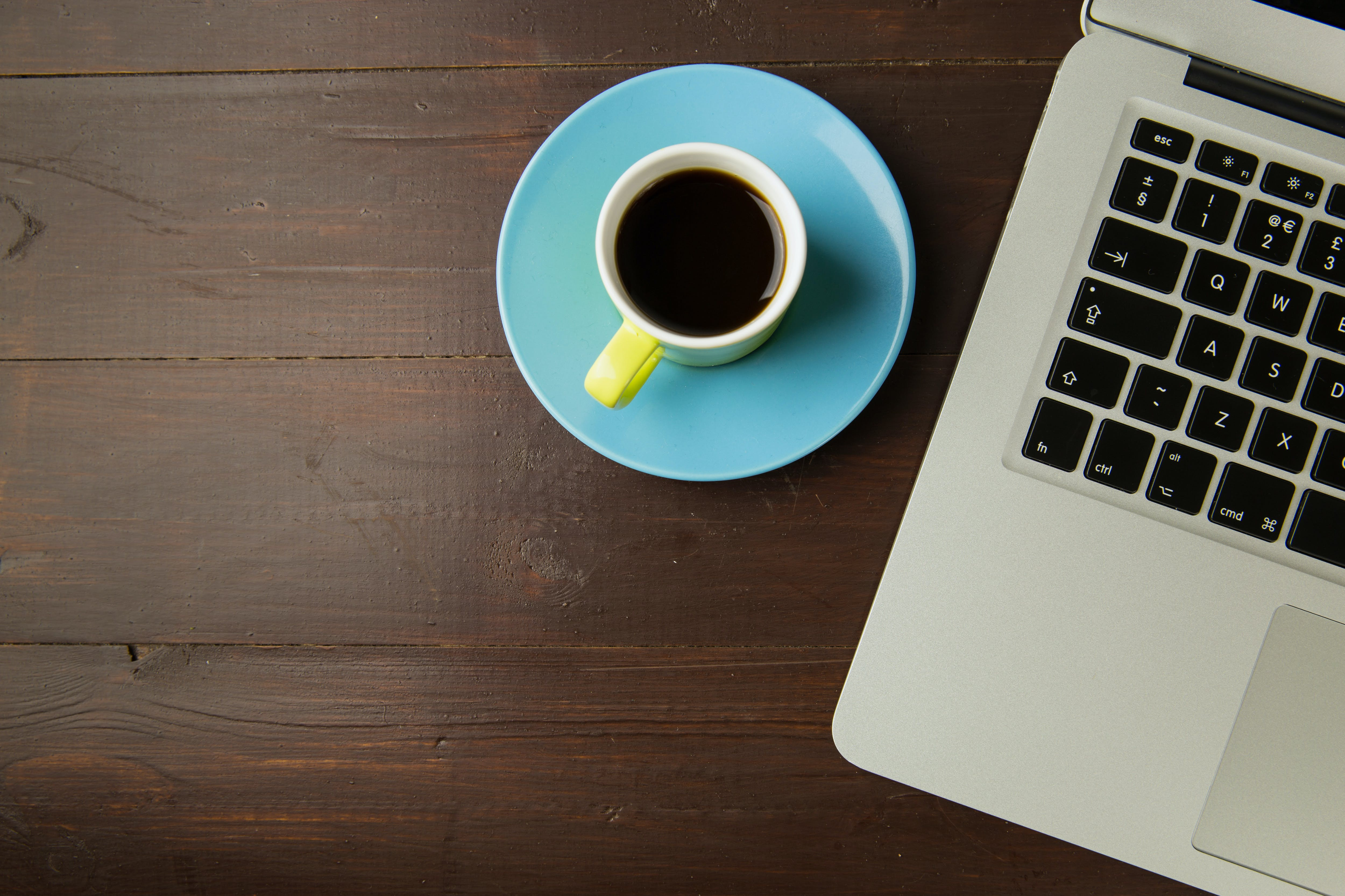 White Ceramic Mug Filled With Coffee Beside the Laptop Computer