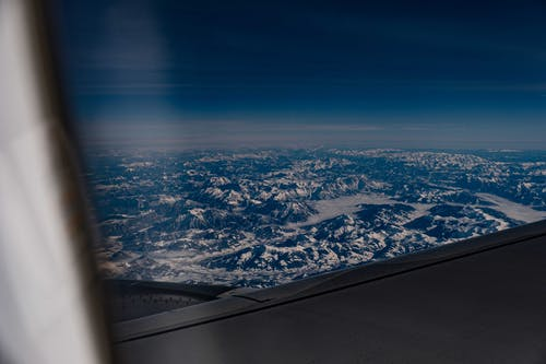 View of tall bare rocks with snow on tops under blue sky with clouds from window of aircraft
