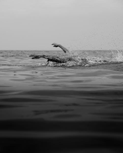 Unrecognizable person swimming in rippling sea