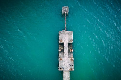 Concrete aged empty pier in blue water of ocean