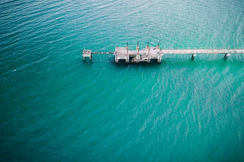 Long gray concrete pier surrounded with rippling water