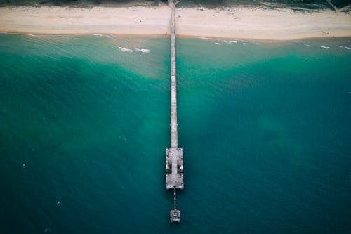 Drone view of long pier near sandy shore washed by turquoise water of blue endless ocean