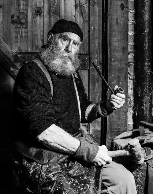 Man in Black Vest and Black Vest Holding a Smoking Pipe