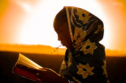 Side view of black female in traditional wear reading book while standing against bright skyline