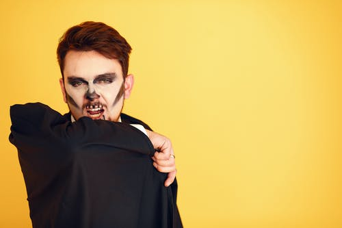 Man with Painted Face in Black Cape Roaring