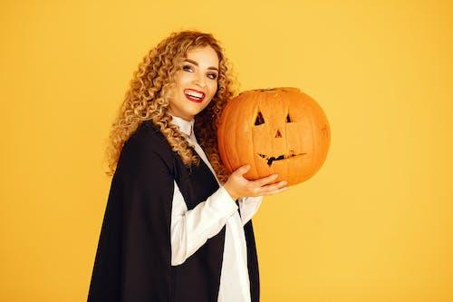 Smiling Woman in Black Coat Holding Pumpkin