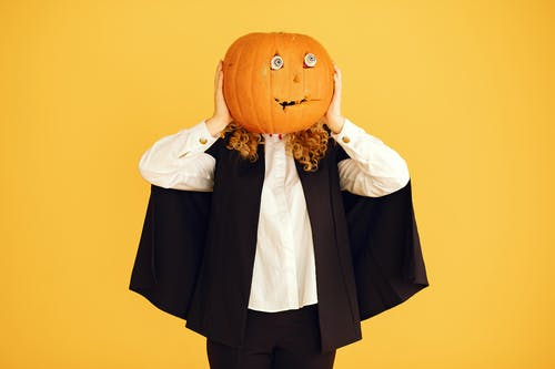 Person Holding a Carved Pumpkin