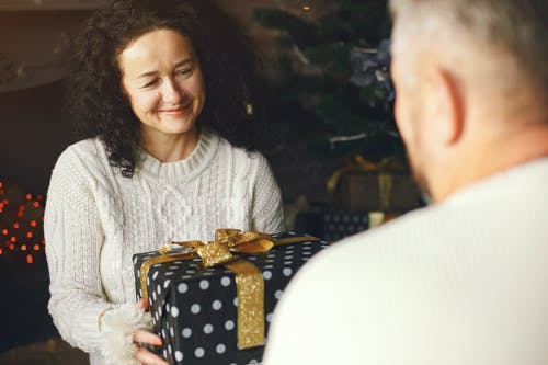 Smiling Wife Receiving a Christmas Gift from Her Loving Husband