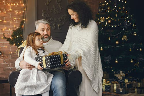 Cute Daughter Receiving a Christmas Present from Her Mother