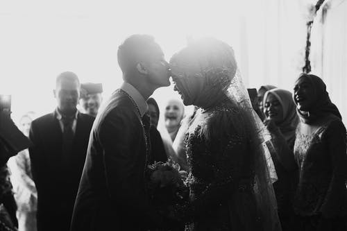 Black and white side view of ethnic man in suit kissing forehead of happy beloved in bridal dress and veil near guests on wedding day