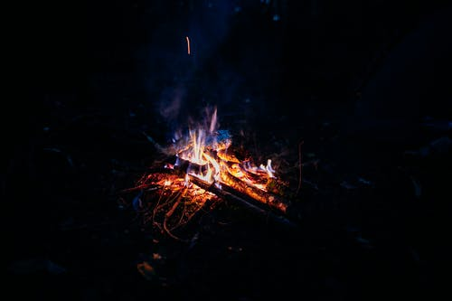 High angle of campfire burning on ground in forest with bright orange flames and smoke at night