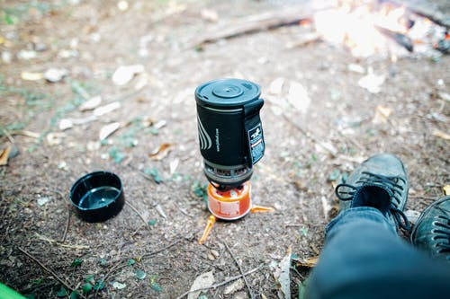 Crop unrecognizable hiker relaxing near campfire and mini camping stove in woods
