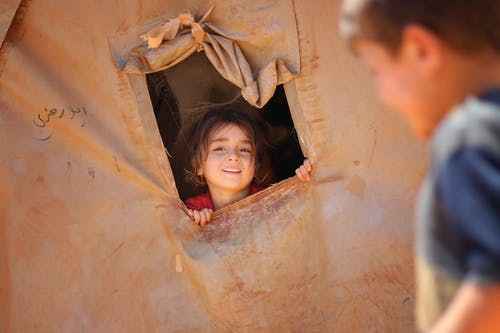 Smiling little ethnic girl looking out of window in tent