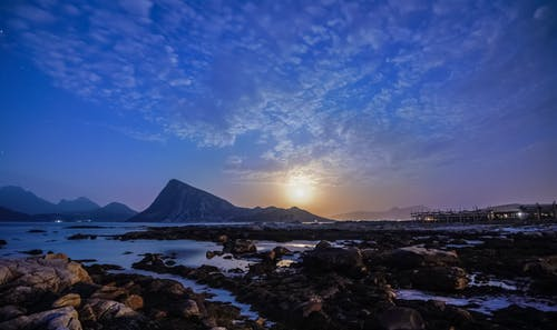 Picturesque view of mountains near ocean under cloudy blue sky with glowing sun in evening