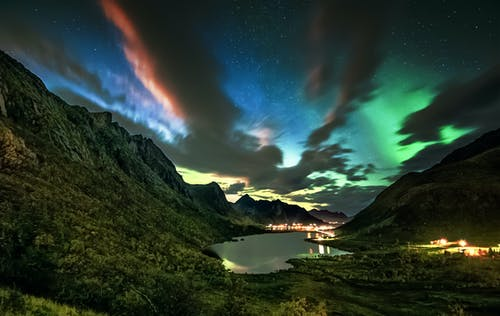 Breathtaking scenery of northern lights over Reine village located on seashore surrounded by green rocky mountains  in Norway