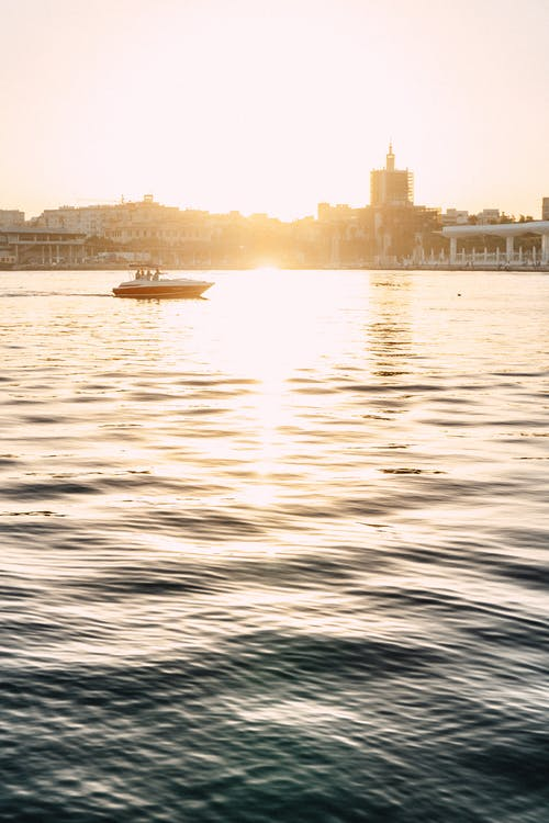 Picturesque view of distant yacht floating on rippling sea near buildings located on coast with sun shining on water surface