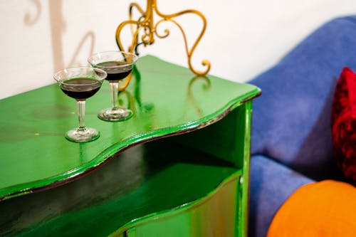Glasses of red wine placed on green cabinet near blue couch  near white wall in cozy light room in daytime
